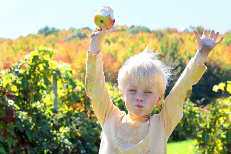 Gelukkig Jong Kind die Fruit eten bij Apple-Boomgaard in de Herfst royalty-vrije stock fotografie