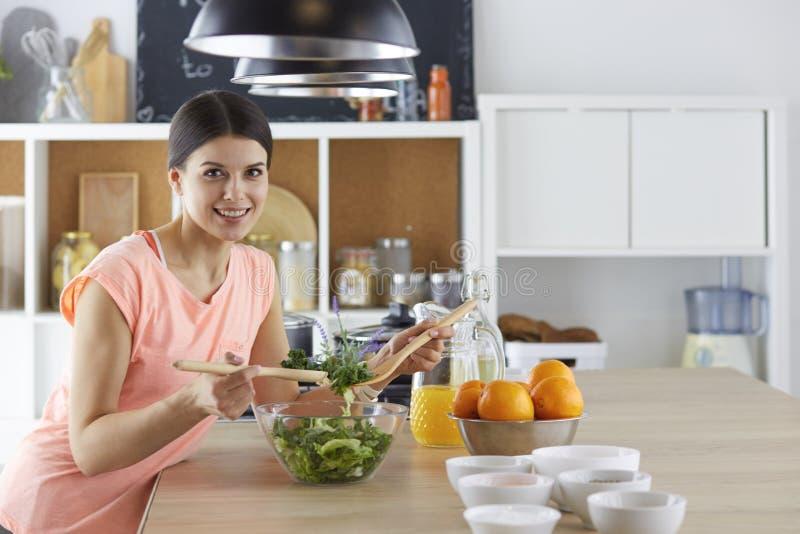 Gelukkig jong kokmeisje die voedsel van greens voorbereiden royalty-vrije stock foto