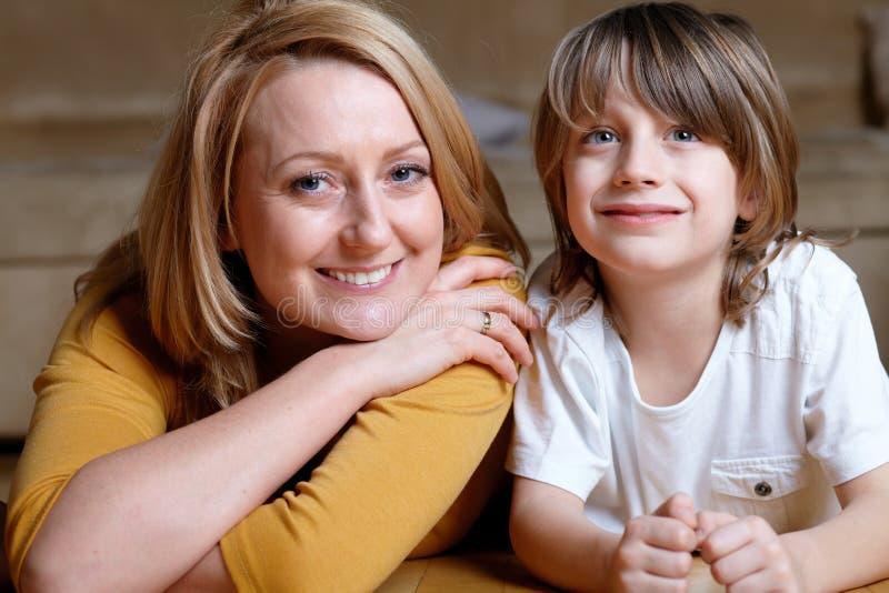 Gelukkig jong mamma dat op vloer met haar zoon ligt royalty-vrije stock foto's