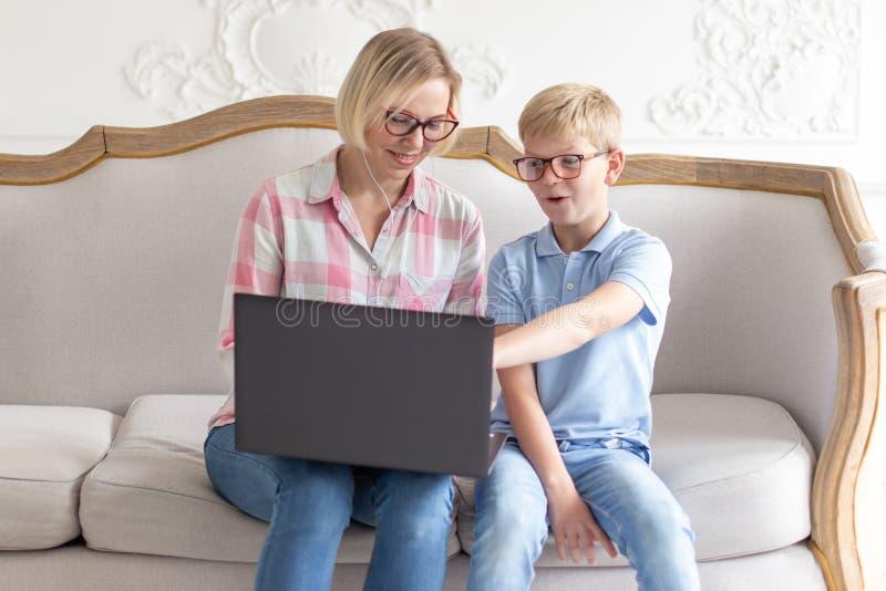 Gelukkig jong mamma en haar zoonszitting op bank en het gebruiken van laptop Jonge jongen die iets tonen aan zijn mamma stock foto's