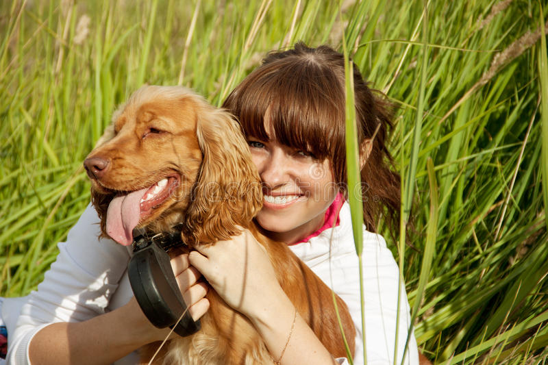 Gelukkig jong meisje dat haar hond omhelst stock afbeelding
