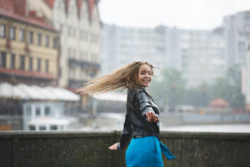 Gelukkig jong meisje in de regen stock afbeelding