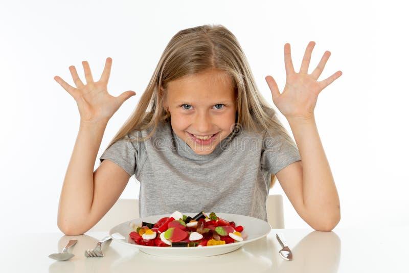 Gelukkig jong meisje die een plaathoogtepunt van suikergoedlollies houden op witte achtergrond stock foto's
