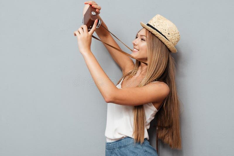 Gelukkig jong meisje die in hoed selfie met retro camera maken royalty-vrije stock foto's