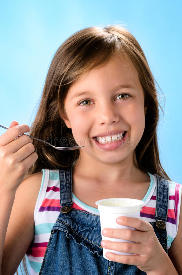 Gelukkig jong meisje die probiotic yoghurt eten royalty-vrije stock foto
