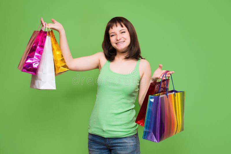 Gelukkig jong meisje met kleurrijke die het winkelen zakken op groene B wordt geïsoleerd royalty-vrije stock afbeeldingen