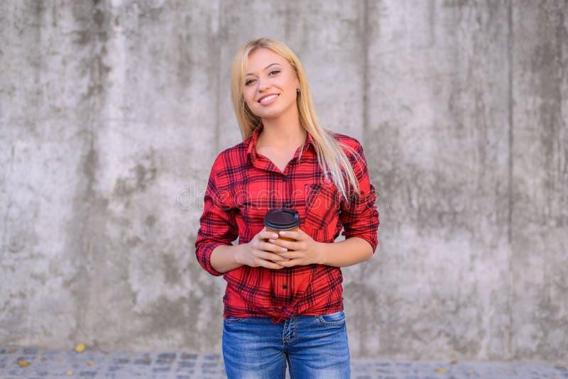 Gelukkig jong meisje met toothy glimlach die in vrijetijdskleding een kop van kop in haar handen houden De grijze achtergrond, sl royalty-vrije stock foto