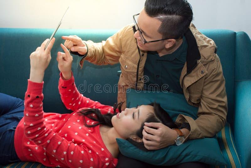 Gelukkig jong ontspannen Aziatisch paar die aan digitale tablet werken stock afbeelding