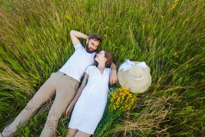 Gelukkig jong ontspannen paar in liefde die op de grasoverheadkosten bepalen stock foto