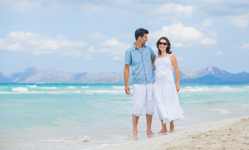Gelukkig jong paar dat op strand loopt royalty-vrije stock fotografie