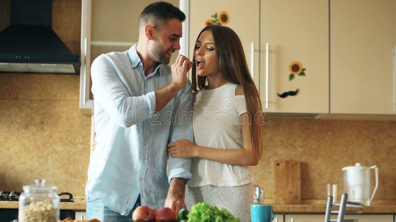 Gelukkig jong paar in de keuken De knappe mens ontmoet en voedt zijn meisje vroege ochtend royalty-vrije stock foto's