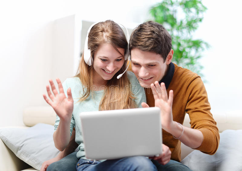 Gelukkig jong paar die door de computer met videopraatje spreken royalty-vrije stock foto's
