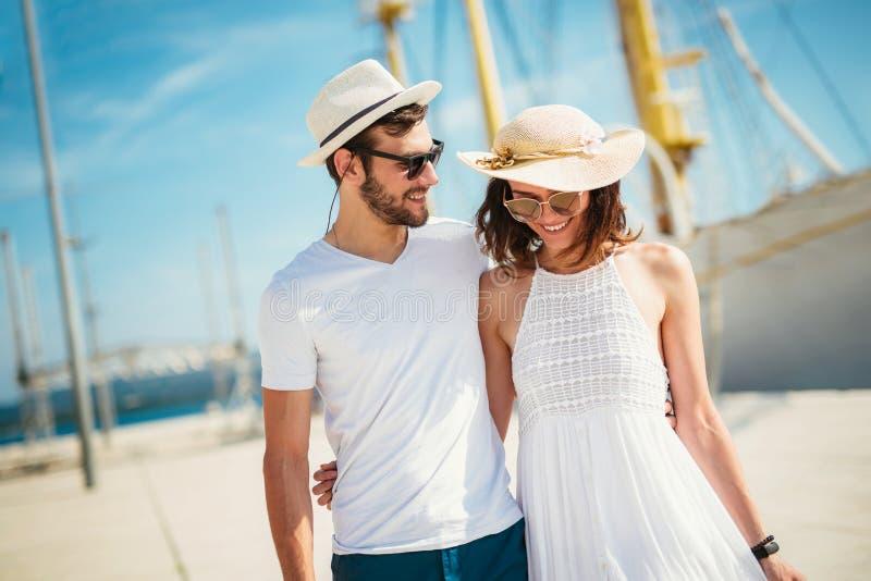 Gelukkig jong paar die door de haven van een toeristische overzeese toevlucht lopen royalty-vrije stock foto