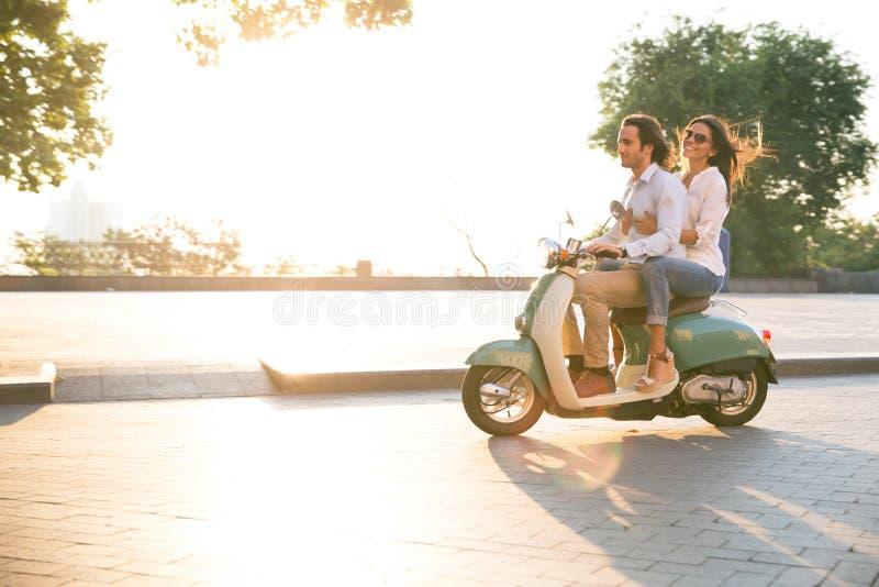 Gelukkig jong paar die een autoped in openlucht berijden stock fotografie