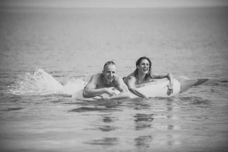 Gelukkig jong paar die en op luchtmatras zwemmen lachen Het concept van de paarvakantie De man en de vrouw op wittebroodsweken, z royalty-vrije stock afbeelding