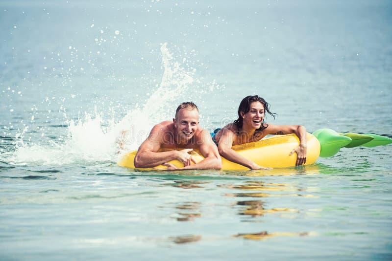 Gelukkig jong paar die en op luchtmatras zwemmen lachen Het concept van de paarvakantie De man en de vrouw op wittebroodsweken, z stock foto