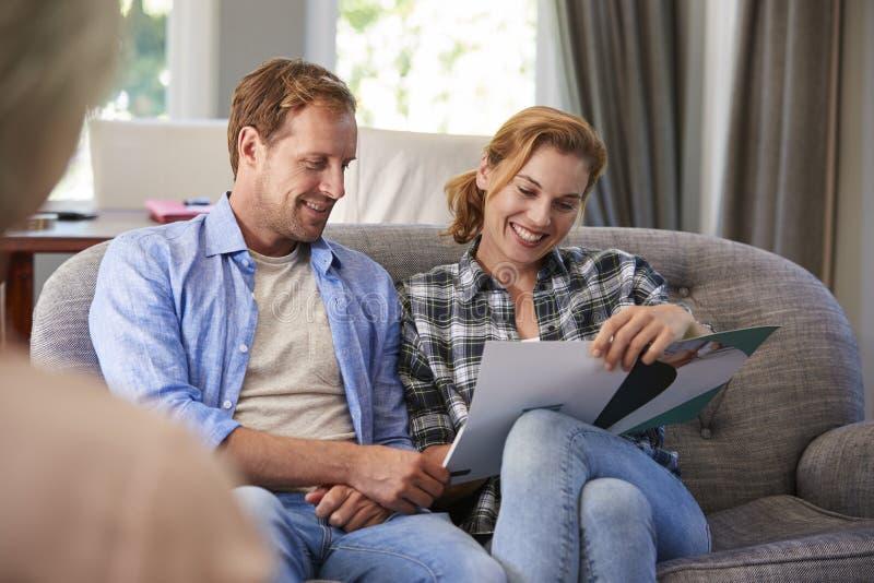 Gelukkig jong paar die financiële raad thuis nemen royalty-vrije stock afbeeldingen