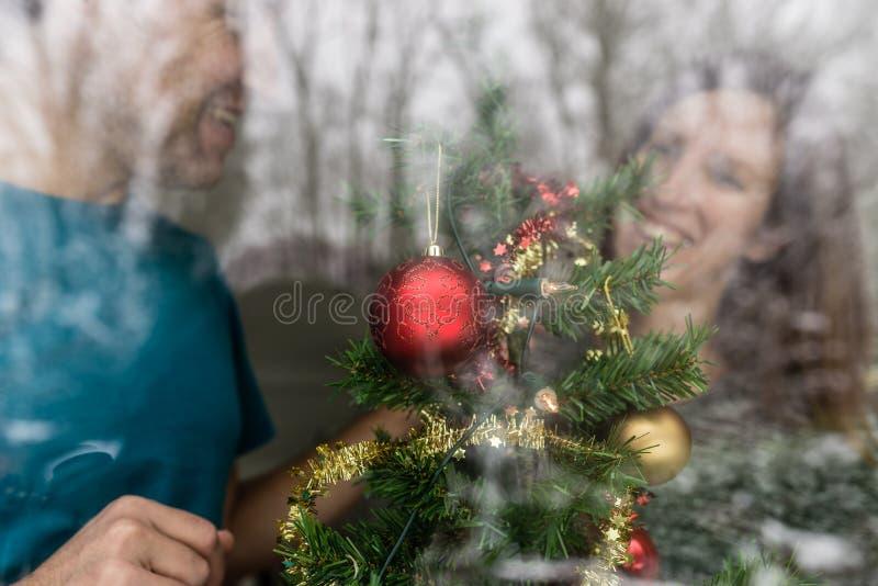 Gelukkig jong paar die Kerstmisboom verfraaien stock afbeelding
