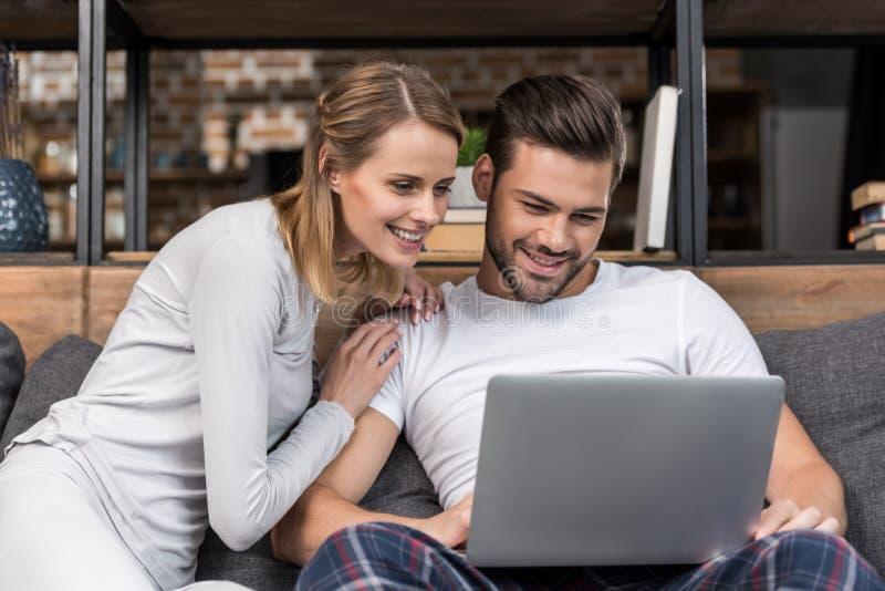 gelukkig jong paar die laptop met behulp van terwijl het zitten op bank stock fotografie
