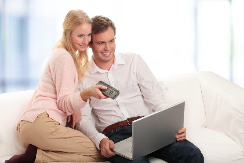 Gelukkig jong paar die laptop in woonkamer met behulp van royalty-vrije stock foto