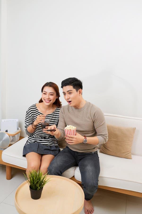 Gelukkig jong paar die op de bank thuis met popcorn liggen die op TV letten royalty-vrije stock afbeeldingen