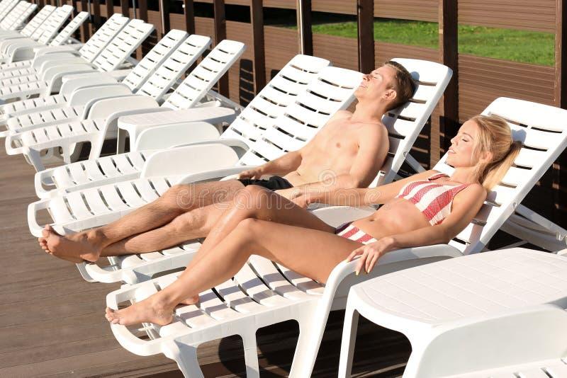 Gelukkig jong paar die op zonlanterfanters bij toevlucht rusten stock foto's