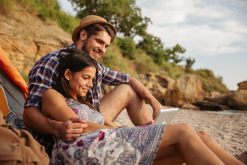 Gelukkig jong paar die pret hebben die bij het strand kamperen stock foto's
