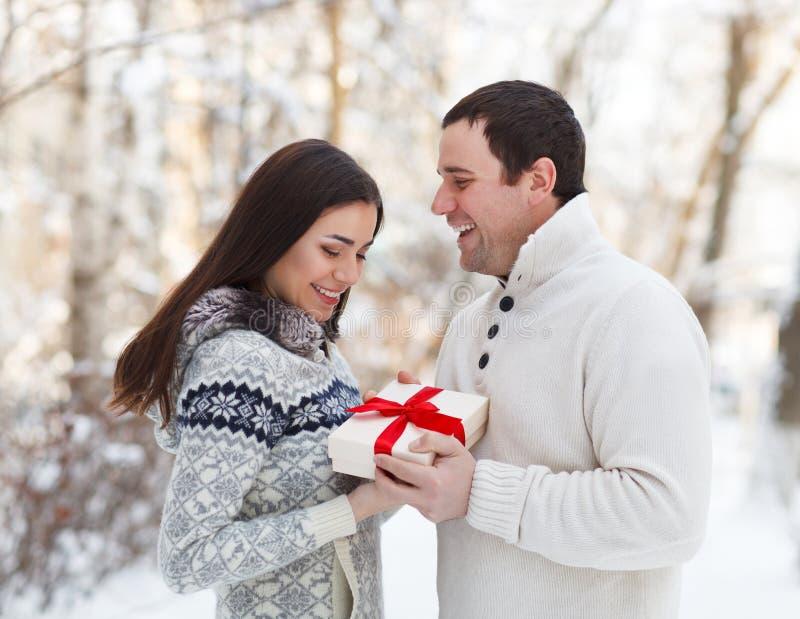 Gelukkig jong paar die pret in het de winterpark hebben stock foto