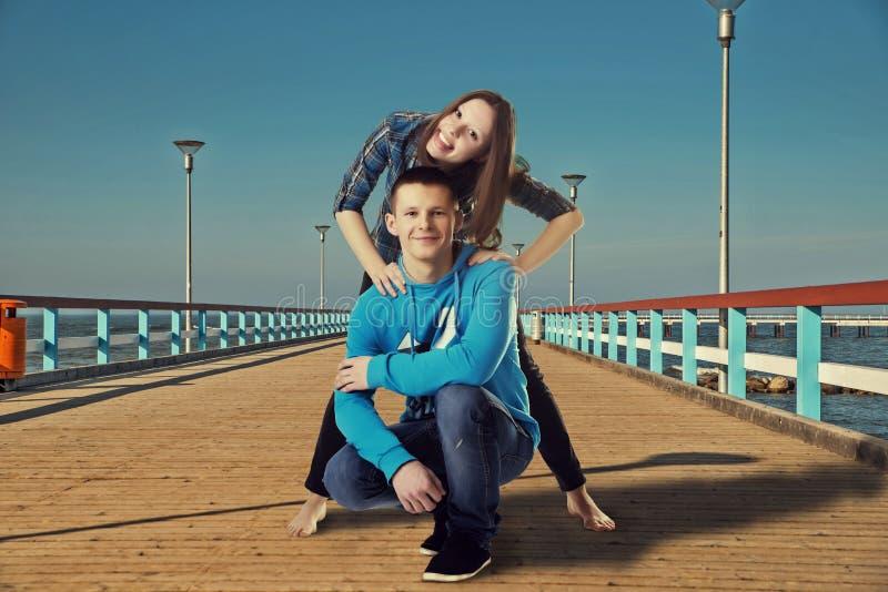 Gelukkig jong paar die pret op de brug hebben stock foto's
