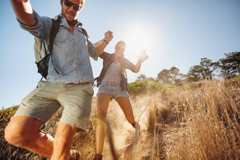Gelukkig jong paar die pret op hun wandelingsreis hebben stock fotografie