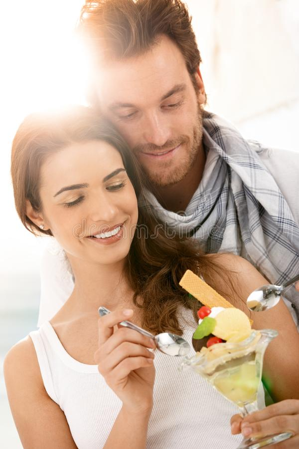 Gelukkig jong paar die roomijs op de zomerstrand eten royalty-vrije stock afbeelding