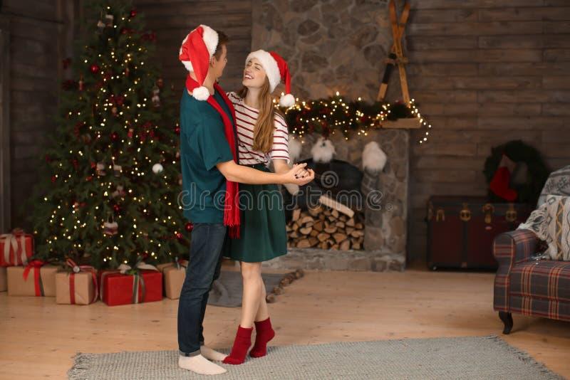 Gelukkig jong paar die die in ruimte dansen voor Kerstmis wordt verfraaid royalty-vrije stock foto