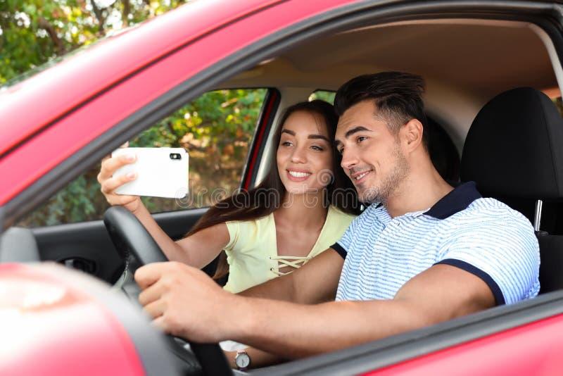 Gelukkig jong paar die selfie in auto nemen stock afbeelding