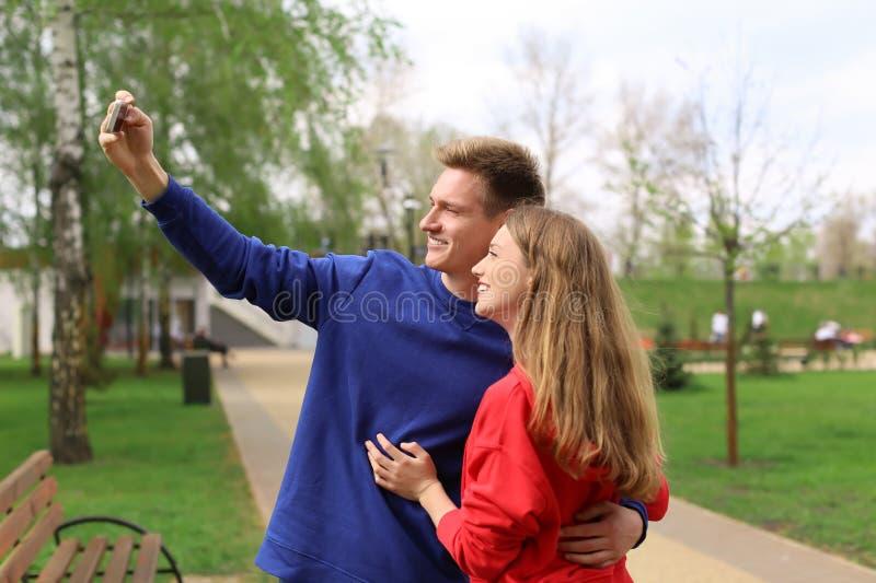 Gelukkig jong paar die selfie in park op de lentedag nemen royalty-vrije stock foto's