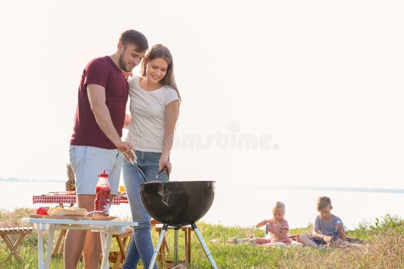 Gelukkig jong paar die smakelijk voedsel bij de barbecuegrill in openlucht koken Familie van vier in het de herfstbos stock afbeeldingen