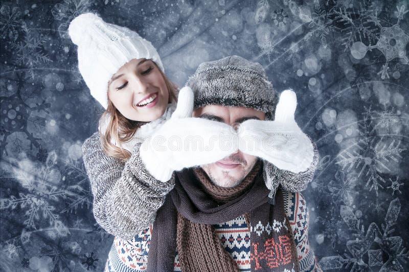 Gelukkig jong paar die sneeuwachtergrond behandelen. stock afbeeldingen