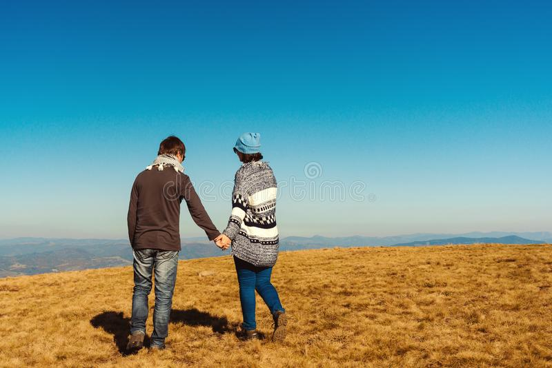 Gelukkig jong paar die van aard genieten bij bergpiek De houdende van paarholding overhandigt blauwe hemelachtergrond Liefde, vri royalty-vrije stock foto