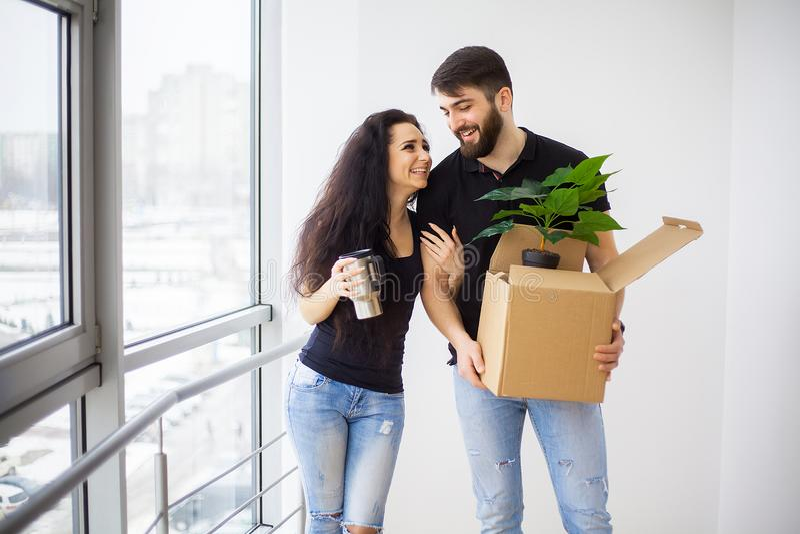 Gelukkig jong paar die zich in nieuwe huis uitpakkende dozen bewegen stock afbeeldingen