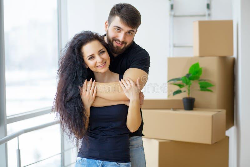 Gelukkig jong paar die zich in nieuwe huis uitpakkende dozen bewegen royalty-vrije stock afbeeldingen