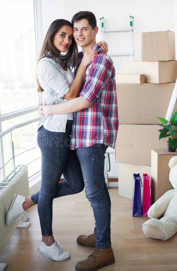 Gelukkig jong paar die zich samen in nieuwe flat bewegen stock fotografie