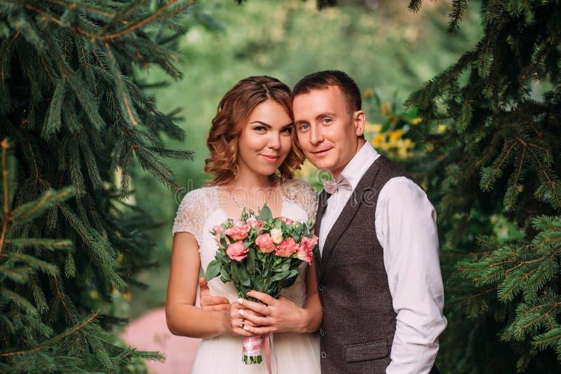 Gelukkig jong paar, een blonde bruid die in lichte witte verbazende huwelijkskleding, boeket van roze bloemen, en bruidegom houde stock fotografie