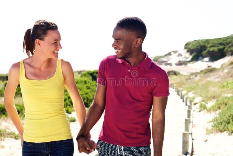 _gelukkig jong paar kijken bij elkaar en glimlachen stock fotografie