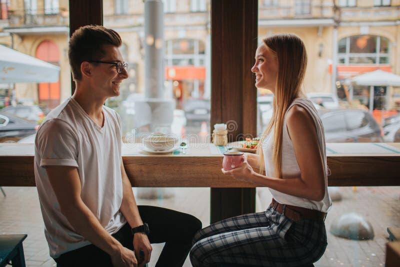 Gelukkig jong paar in liefde die een aardige datum in een bar of een restaurant hebben Zij die sommige verhalen vertellen over zi stock afbeeldingen