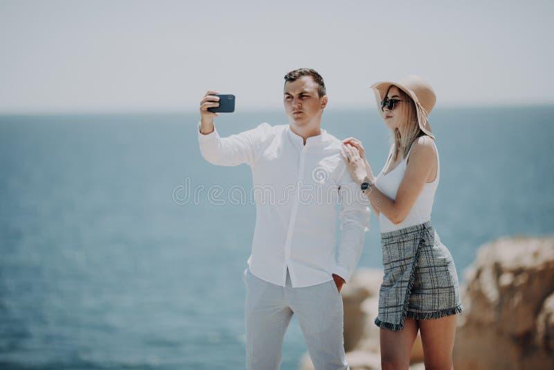 Gelukkig jong paar in liefde die selfie met mobiele telefoon op strand nemen royalty-vrije stock afbeelding