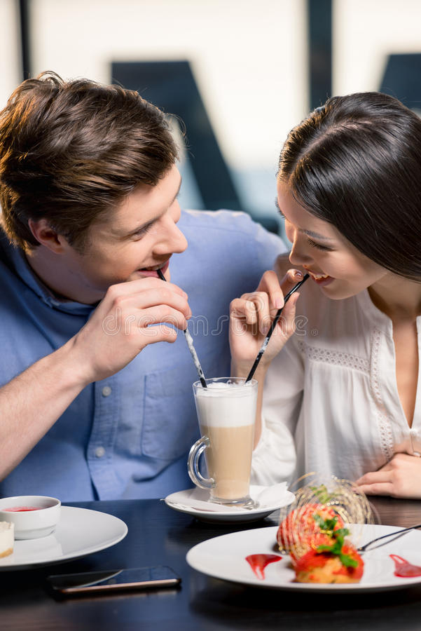 Gelukkig jong paar in liefde op romantische datum in restaurant stock afbeelding