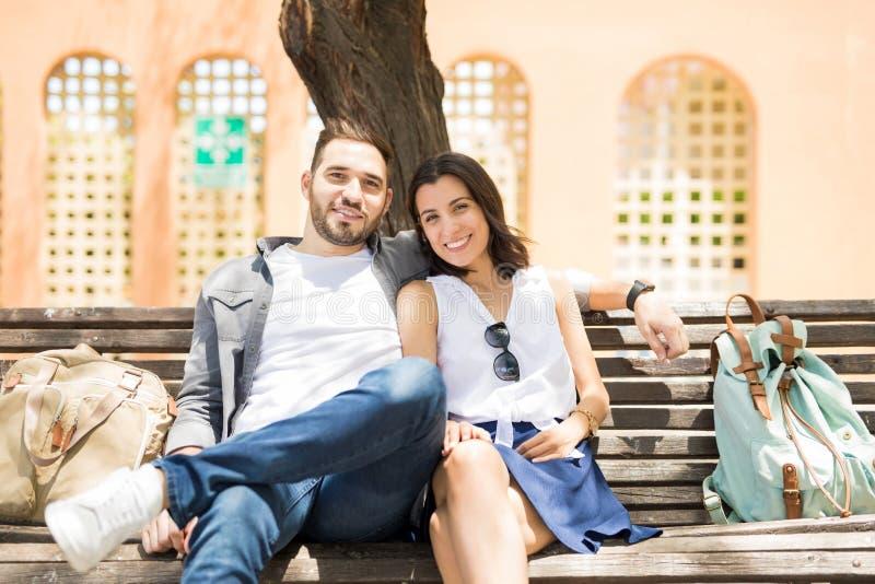 Gelukkig jong paar in liefdezitting op straatbank en het kijken a stock fotografie
