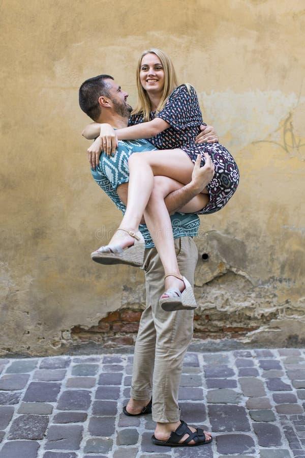 Gelukkig jong paar, man holdingsvrouw in zijn wapens Liefde stock afbeeldingen