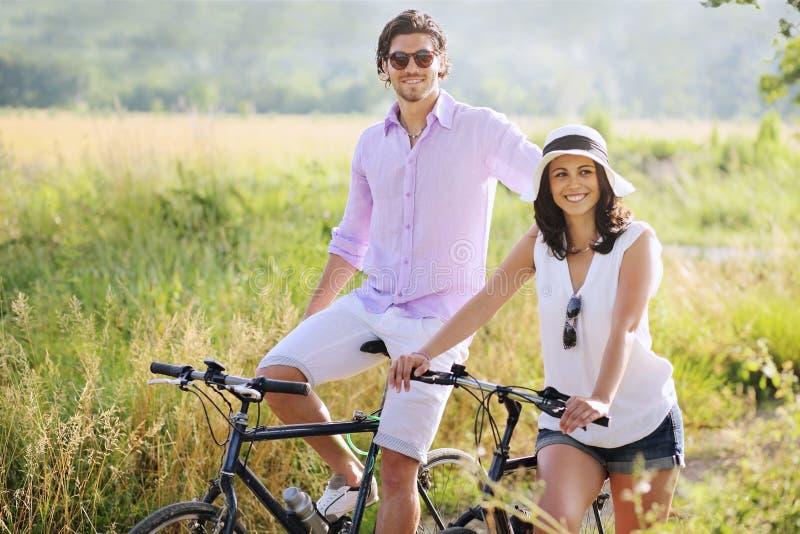 Gelukkig jong paar met fietsen stock foto's