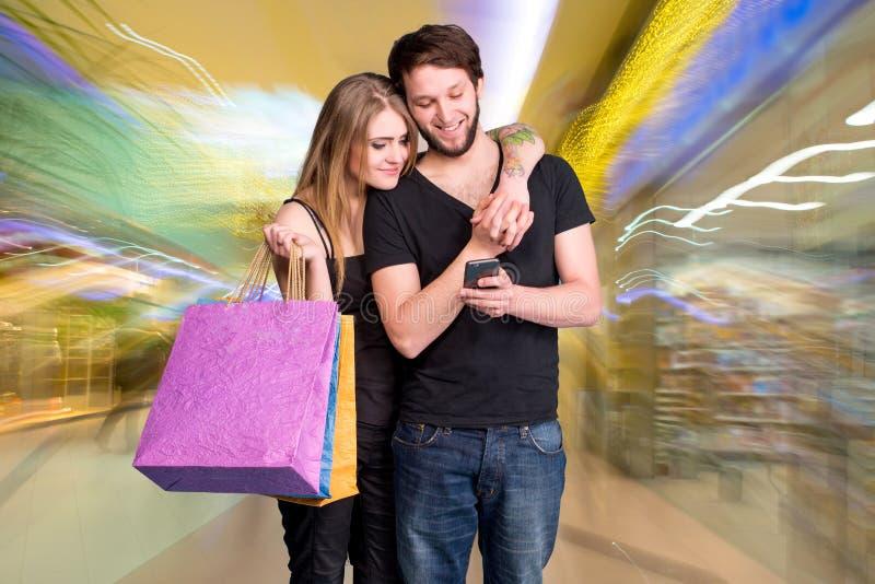 Gelukkig jong paar met het winkelen zakken stock foto