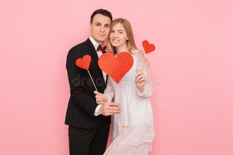 Gelukkig jong paar, met 3 rode document harten, die op een kind, op een roze achtergrond wachten royalty-vrije stock foto's